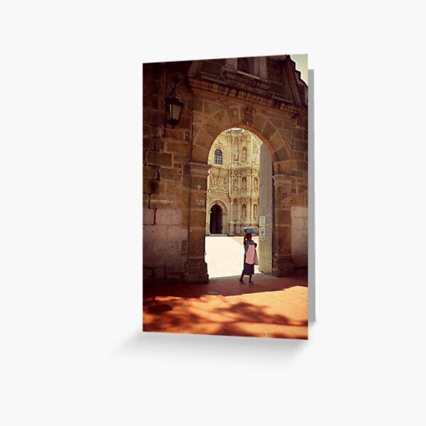 A woman carries bread through a church yard, Oaxaca, Mexico Greeting Card