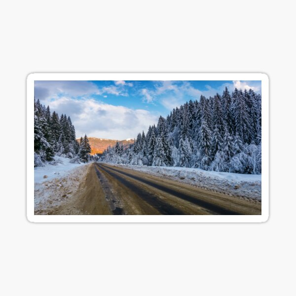 snowy road through mountains in evening Sticker