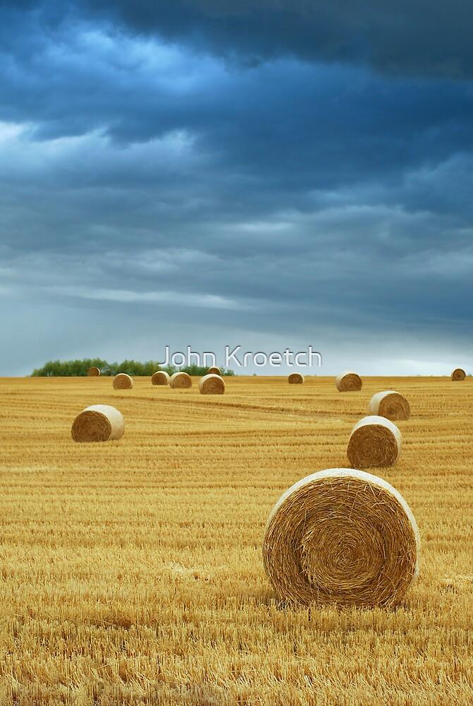 Hay Bales in Field with Stormy Sky by John Kroetch