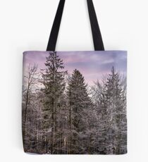 forest in hoarfrost on snowy hillside at dawn Tote Bag