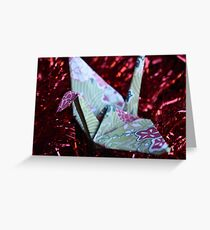 Pink and green patterned paper crane on red tinsel Greeting Card