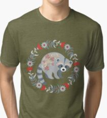 Raccoon in a frame of leaves and flowers. Style folk art.  Tri-blend T-Shirt