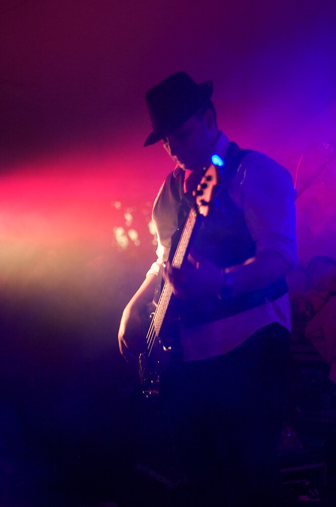 bass player under lights by Paul Hoefgen