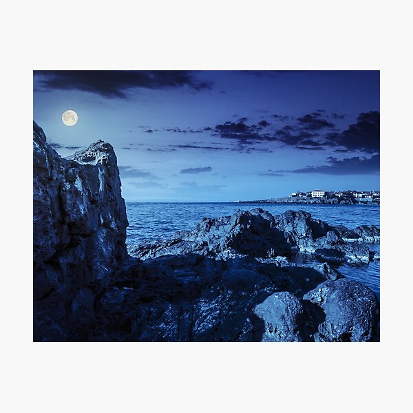 sea bay with boulders and old city at night Photographic Print