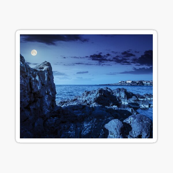 sea bay with boulders and old city at night Sticker