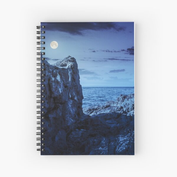 sea bay with boulders and old city at night Spiral Notebook