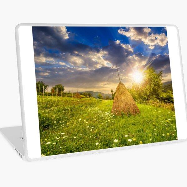 field with haystacks on hillside at sunset Laptop Skin