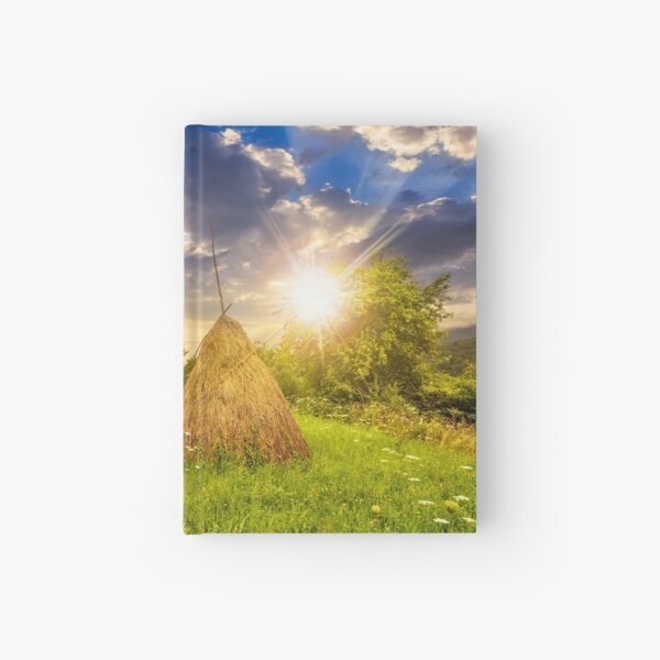 field with haystacks on hillside at sunset Hardcover Journal