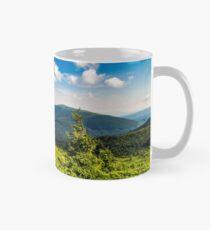 conifer tree with stone on hillside Mug