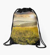 village on hillside meadow at sunset Drawstring Bag
