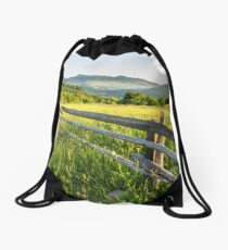 fence on hillside meadow in mountain Drawstring Bag