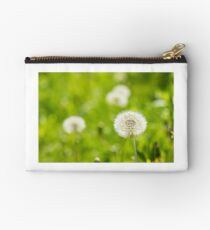 white dandelion on green grass blur background Studio Pouch