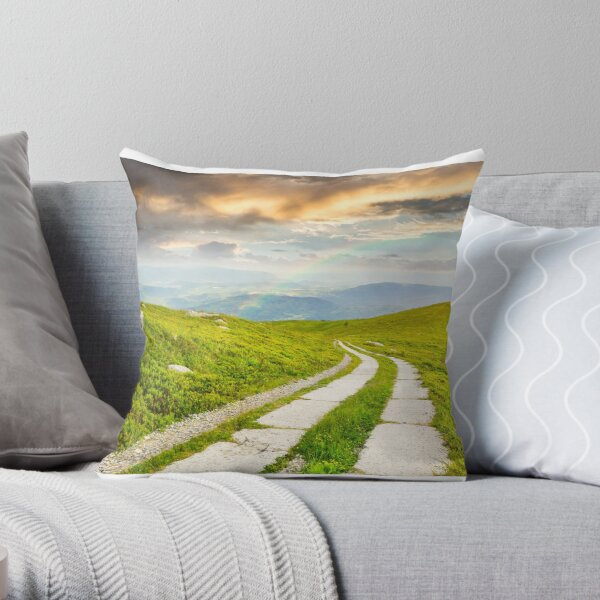 road on a hillside near mountain peak Throw Pillow