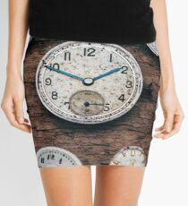 Tiny watch parts on a wooden background Mini Skirt