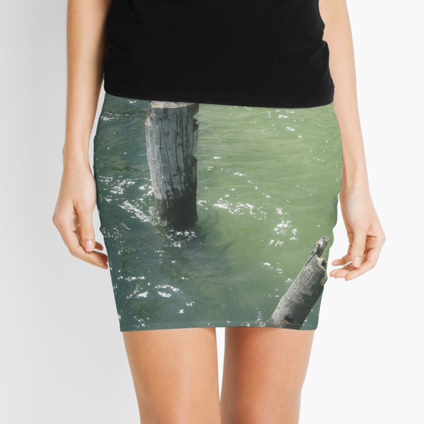 Old wooden piles sticking out of sea water Mini Skirt