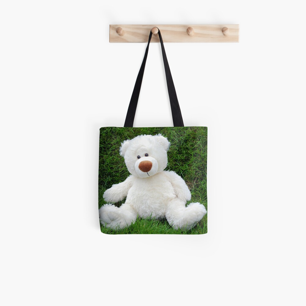 White teddy-bear sitting in grass Tote Bag