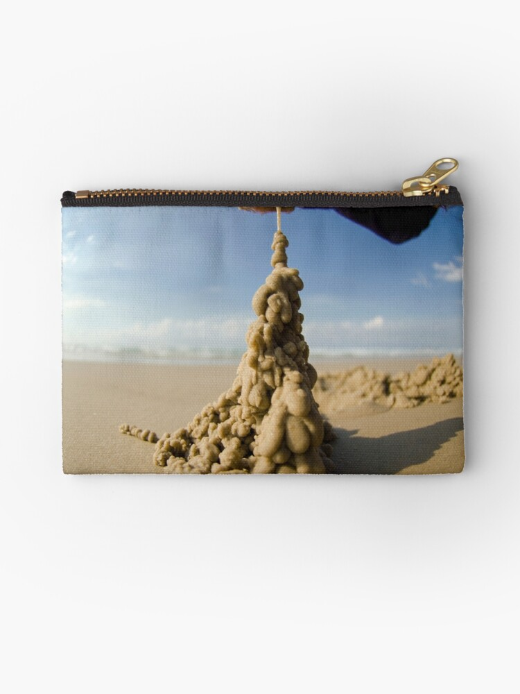 Hand dripping wet sand onto a sand castle on the beach by PhotoStock-Isra