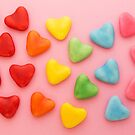 Heart-shaped colorful candy arranged in rainbow colors, on a pink background by Karin Elizabeth