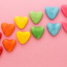 Heart-shaped Candy arranged in rainbow order on a pink background by Karin Elizabeth