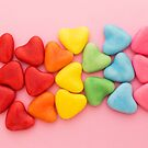 Heart-shaped multi-colored candy ordered in rainbow colors and shape on a pink background by Karin Elizabeth