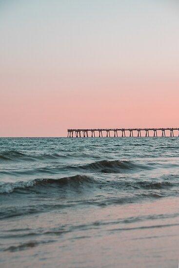 Rosafarbener Himmel mit Promenade entlang dem Ozean von Claire Andrews
