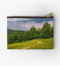dirt road leads in to the forest on overcast day Studio Pouch
