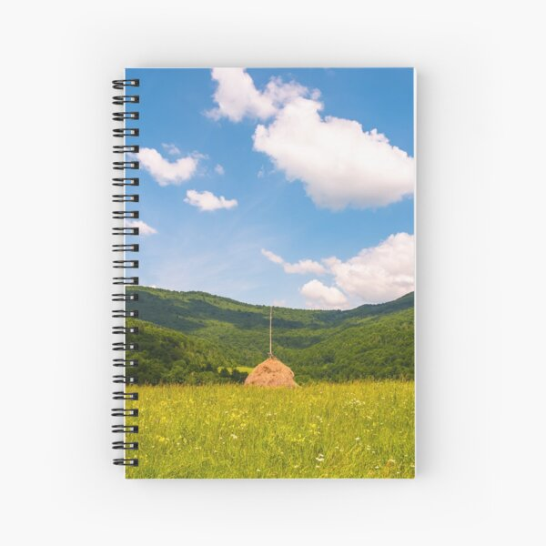 haystack on a grassy pasture in mountains Spiral Notebook