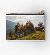 fence along the grassy hillside Studio Pouch