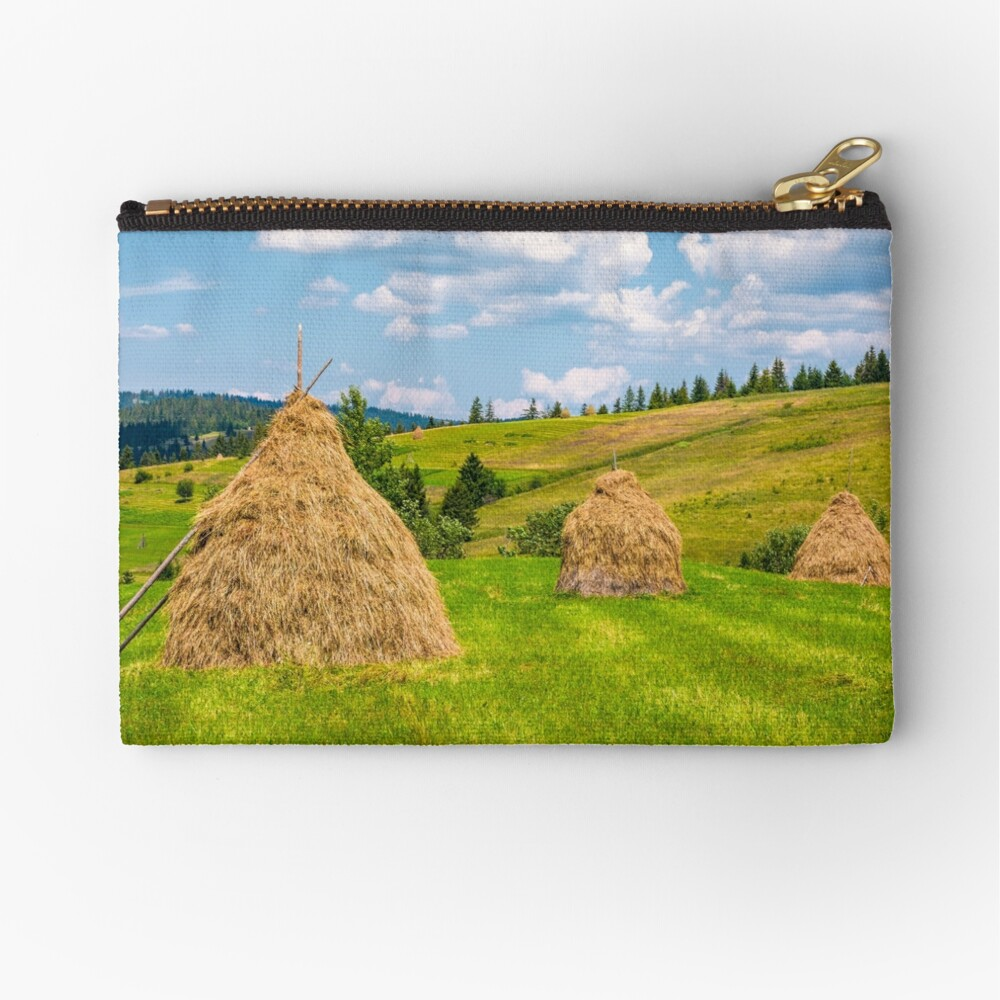 haystacks in a row on a grassy field Zipper Pouch