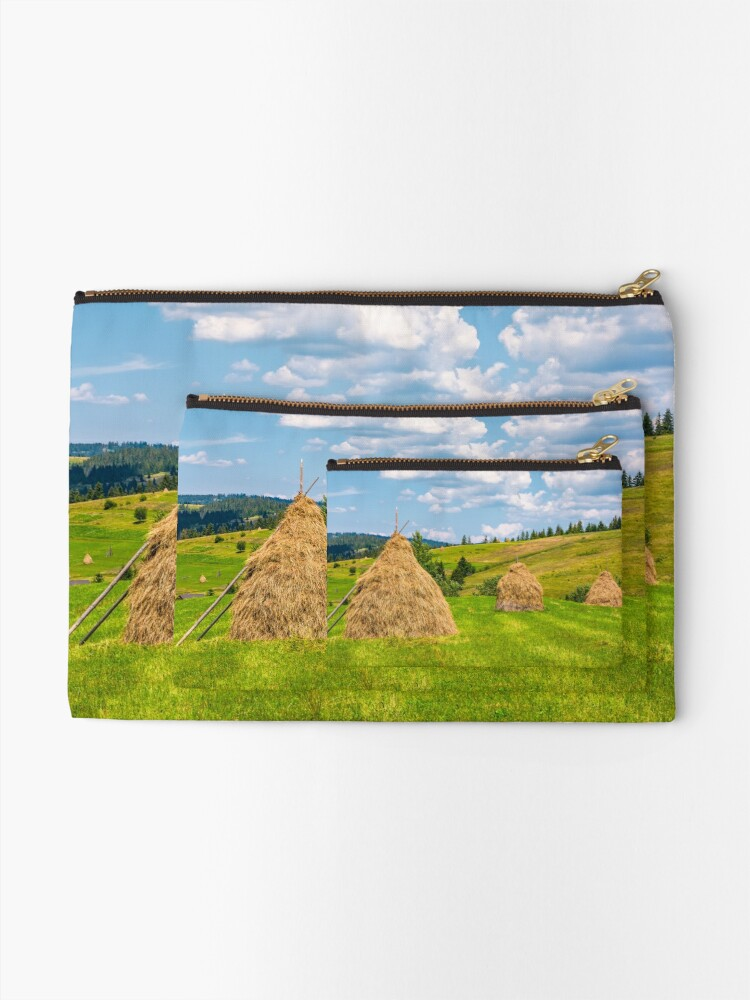 Alternate view of haystacks in a row on a grassy field Zipper Pouch