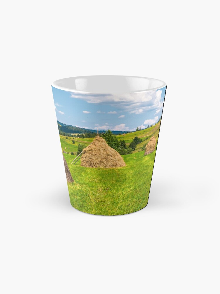 Alternate view of haystacks in a row on a grassy field Mug
