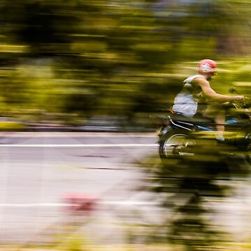 A motorcyclist driving quickly through the trees by clemphoto