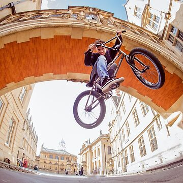 A BMX rider does a jump underneath an arch in Oxford by clemphoto