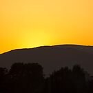 Deep orange sunset with nimbus glow sinking below mountain silhouette  by Rod Raglin