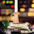 A bass guitar lying flat,blurring into a background of recording studio lights by Adam Calaitzis