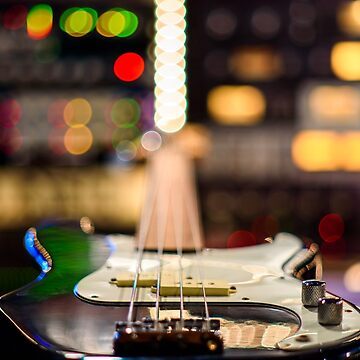 A bass guitar lying flat,blurring into a background of recording studio lights by adamcal