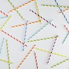 Colorful paper straws on white background by Adam Nixon