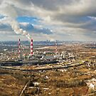 Aerial view of power plant under cloudy sky by Lukasz Szczepanski