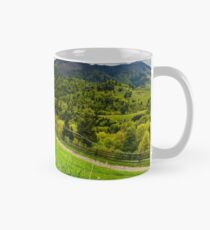 grassy fields on forested hills Mug