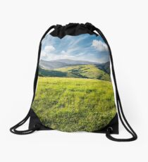 grassy meadow in mountains Drawstring Bag