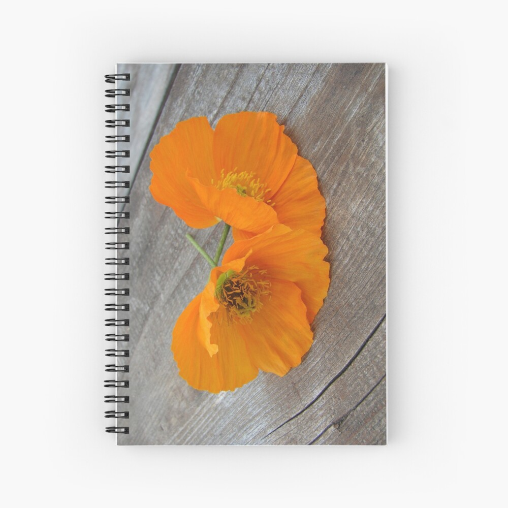 Orange flowers on a wooden table Spiral Notebook
