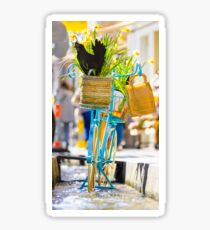 Blue bicycle with a basket full of yellow daffodils Sticker
