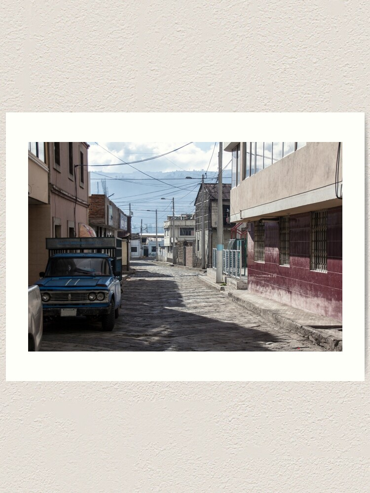Alternate view of Empty quiet winding cobblestone street in Guamote, Ecuador with blue truck, red tile building, power lines and street lamps Art Print