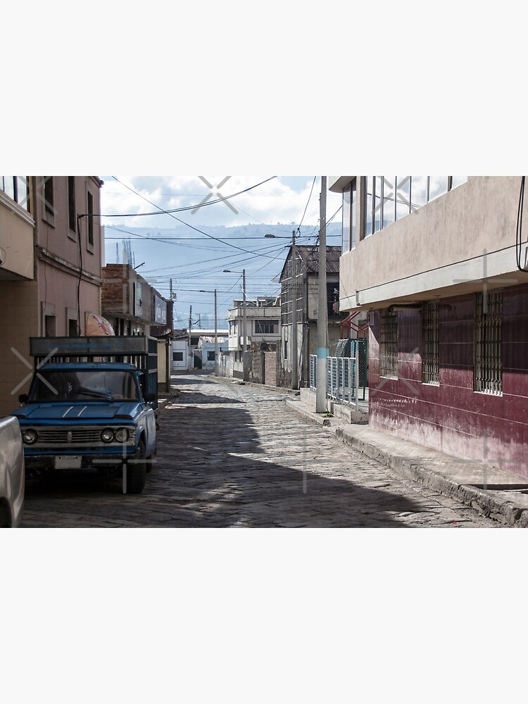 Empty quiet winding cobblestone street in Guamote, Ecuador with blue truck, red tile building, power lines and street lamps by kpander