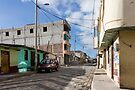 Empty cobblestone street going up hill with concrete block building and houses in Guamote, Ecuador by Kendall Anderson