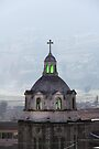 Guamote, Ecuador catholic church spire with cross, with green glowing stained glass windows by Kendall Anderson