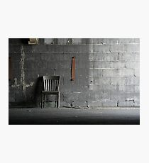 Abandoned wooden grey chair resting against a grey concrete block wall in an abandoned carbide graphite industrial factory Photographic Print