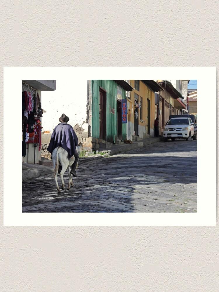 Alternate view of Man wearing purple poncho rides donkey up cobblestone street in Guamote, Ecuador Art Print