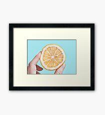 Juicy lemon on a blue background Framed Print