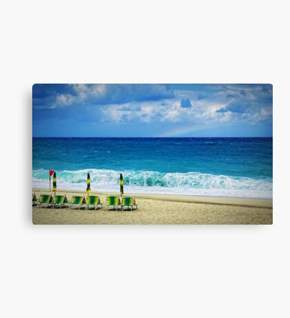 Deck chairs on beach with faraway rainbow Canvas Print